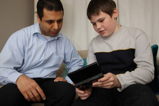 A 10 to 11-year old boy talking to an adult and showing him, what looks like a video game, on a mobile device