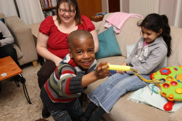Foster carer plays with a young girl and boy who look happy