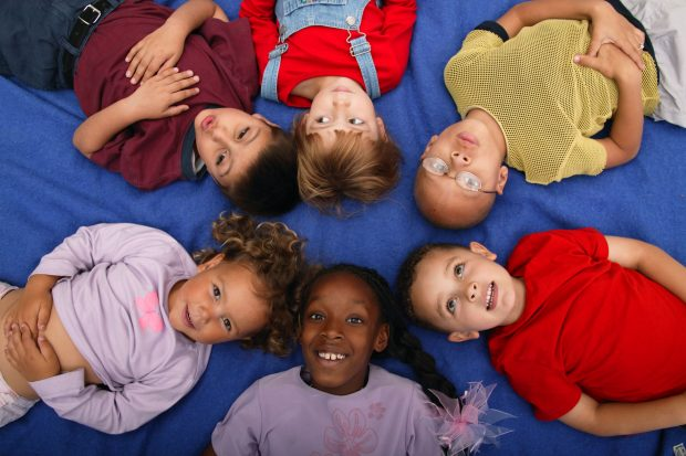 children lying down in a circle looking happy