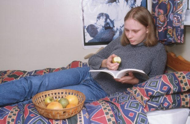 Teenage girl sat on a bed, reading a book