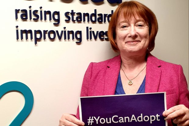"Yvette stanley holding a placard saying ""you can adopt"""