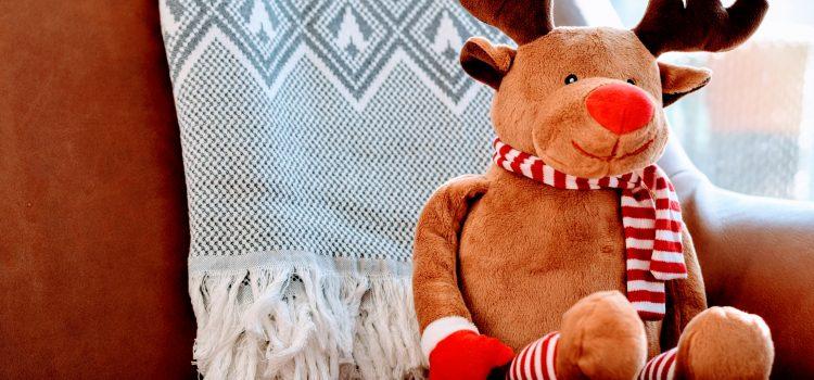 reindeer cuddly toy sat on a sofa