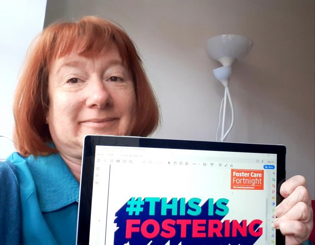Picture of Yvette Stanley holding a sign to celebrate Foster Care Fortnight