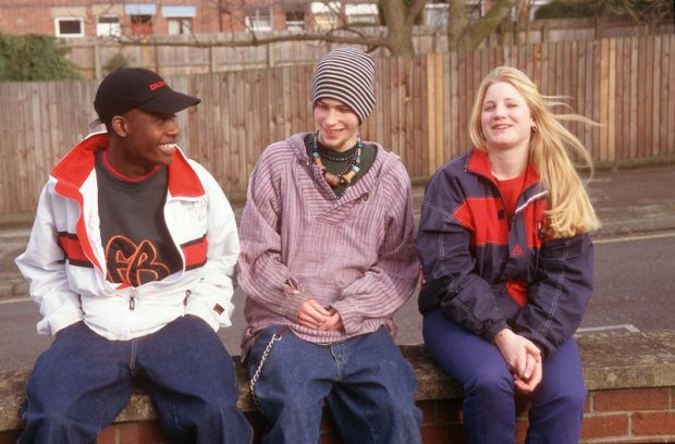 three teenagers sat on a wall, smiling and laughing