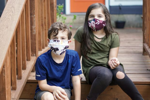 Two young children wearing COVID masks