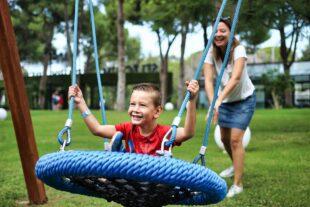Carer pushing smiling boy in a swing