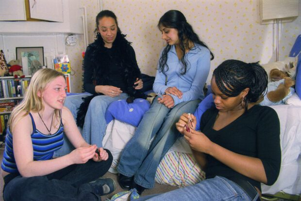 Group of teenage girls sitting together in bedroom painting nails and chatting,